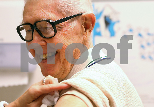 Kyle Bursaw – kbursaw@shawmedia.com<br /> <br /> Harry Husa cracks a smile as public health nurse Patti Burke puts a bandage on Husa's arm where he received an influenza vaccination at the DeKalb County Health Department on Thursday, Sept. 22, 2011.