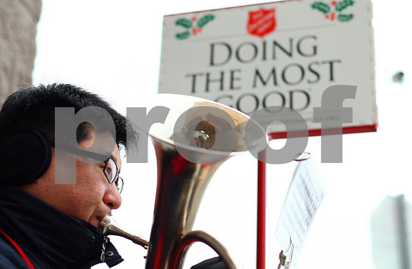 Kyle Bursaw – kbursaw@shawmedia.com<br /> <br /> Michael Cho, a captain with the DeKalb Salvation Army, plays Christmas tunes in lieu of ringing a bell by one of the red kettles outside of Wal-Mart in DeKalb, Ill. on Thursday, Dec. 15, 2011.