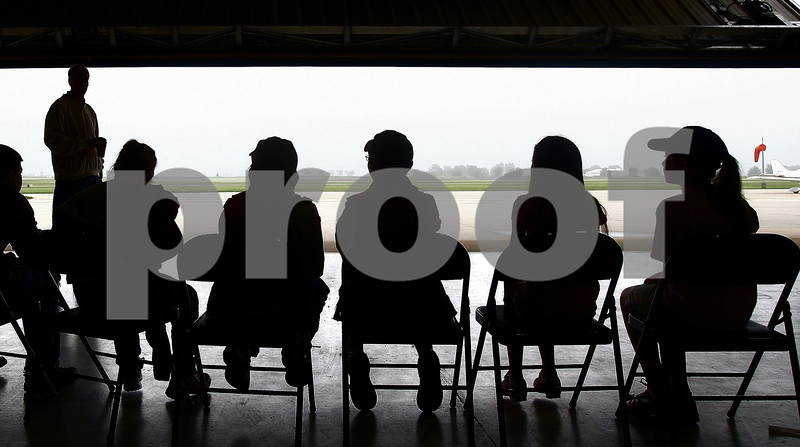 Kyle Bursaw – kbursaw@daily-chronicle.com<br /> <br /> Children at the EAA Young Eagles Rally sit in front of the hangar door at DeKalb taylor Municipal Airport. Foggy conditions that prevented them from being able to fly with pilots as scheduled on Saturday, June 11, 2011.