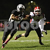 Rob Winner – rwinner@shawmedia.com<br /> <br /> Kaneland's Jesse Balluff (left) carries the ball as Yorkville's Brian McCue gets a hand on him during the first quarter in Maple Park, Ill., on Friday, Oct. 7, 2011.