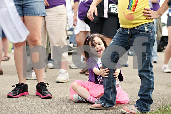 Rob Winner – rwinner@daily-chronicle.com<br /> <br /> DeKalb resident and cancer survivor Raegan Mann, 4, grabs at the leg of her cousin, Emily Pederson, 7, before the survivors lap during the Relay for Life of DeKalb County event on Friday evening in Sycamore.