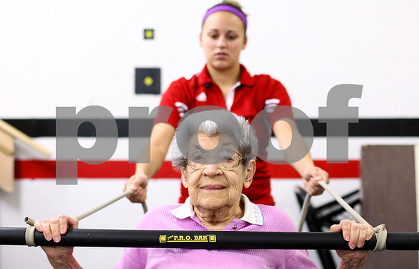 Kyle Bursaw – kbursaw@shawmedia.com<br /> <br /> Rose Marie King, 94, pushes against the resistance of Jenna Capps, a Northern Illinois student majoring in athletic training. Capps helped King through a routine of exercises in the fitness center at Oak Crest on Friday, Nov. 18, 2011.