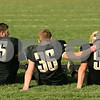 Rob Winner – rwinner@shawmedia.com<br /> <br /> Sycamore seniors Devin Nolley (65), Scott Baker (36) and Brayden Gallimore sit near the north end zone after their Class 5A playoff loss to Rochelle in Sycamore on Saturday, Nov. 5, 2011.