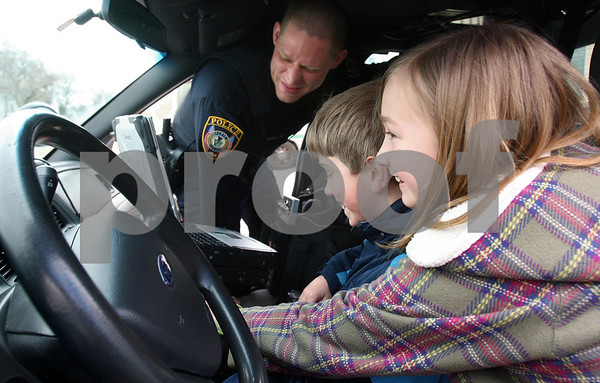 "Kyle Bursaw – kbursaw@daily-chronicle.com<br /> <br /> Officer Todd Wells shows Faith Hendley, 11 and her brother Lucas, 9, the inside of a DeKalb police squad car. Faith, won the Carmike Market Square Cinema's ""What I would do if I was sheriff of DeKalb"" essay contest and got a tour of the police department and the prize of being 'Sheriff of DeKalb' for one day."