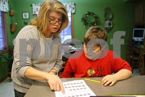 Rob Winner – rwinner@daily-chronicle.com<br /> <br /> Barb Castritsis helps her son, Michael Castritsis, 11, with his homework at their Sycamore home on Tuesday evening. Barb is involved with a support group which has been created for parents of special education students within the Sycamore school district.