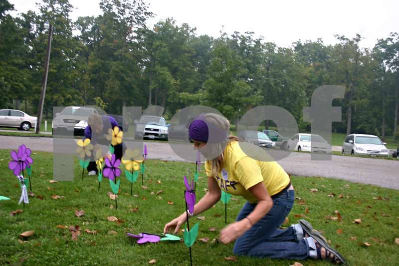 """Kelly Schultz, special events manager for the Alzheimer's Association's Greater Illinois Chapter, and volunteers stick flower pinwheels in the ground Sunday outside the Hopkins Park shelter during DeKalb's first-ever Walk to End Alzheimer's. The flowers, """"planted"""" to create a Promise Garden, represented those involved with the walk who have Alzheimer's, those who care for someone with the disease or those who have lost someone to Alzheimer's. <br /> <br /> Caitlin Mullen - cmullen@shawmedia.com"""
