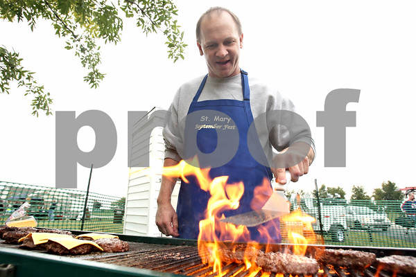 Rob Winner – rwinner@shawmedia.com<br /> <br /> Volunteer Todd Plumley from the Catholic Church of St. Patrick in Rochelle cooks up some hamburgers on the grill as September Fest kicked off at St. Mary School in DeKalb on Friday, Sept. 23, 2011.