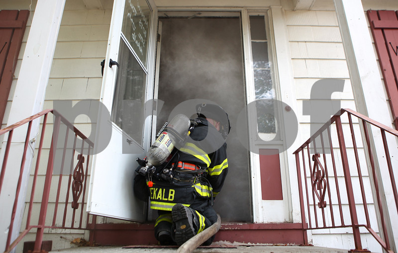 Kyle Bursaw – kbursaw@shawmedia.com<br /> <br /> Firefighter Steve Cruz crawls into a building on Oak Street filled with theatrical smoke with a hose. The DeKalb Fire Department was using the building for training on Tuesday, Oct. 18, 2011.