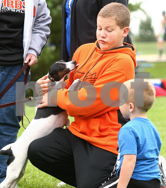 Kyle Bursaw – kbursaw@daily-chronicle.com<br /> <br /> Leo jumps up to lick Ian Kowalski, 13, at Storm Dayz in Sycamore Park on Friday, June 24, 2011 as Sean Kowalski, 4, looks on. Kathy VonBergen holds Leo's leash, but Leo belongs to Kishwaukee Valley Storm player Rachel Lesorgen, who was playing in a softball game at the time.