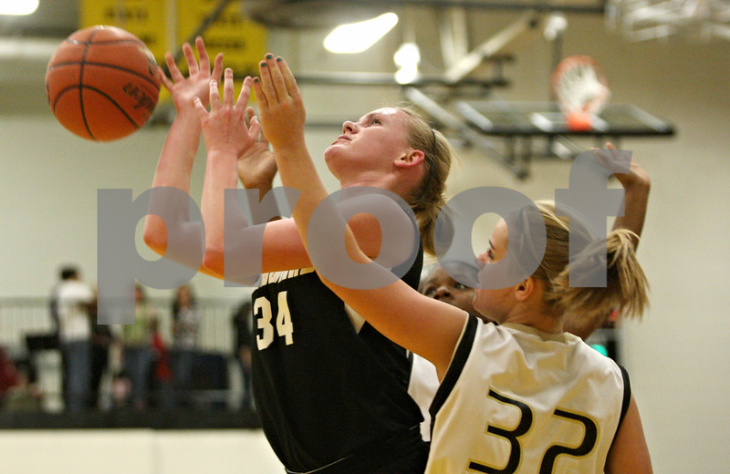 Rob Winner – rwinner@shawmedia.com<br /> <br /> Kaneland's Kelly Evers (34) is fouled by Sycamore's Jessica Mollman (32) during the second quarter in Sycamore on Friday, Dec. 9, 2011.