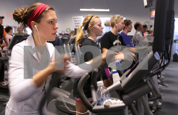 Kyle Bursaw – kbursaw@daily-chronicle.com<br /> <br /> Hannah Flora (left) and many others work out on the elliptical machines at the Kishwaukee YMCA on Friday, Dec. 31, 2010.