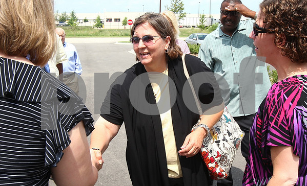 Kyle Bursaw – kbursaw@daily-chronicle.com<br /> <br /> Lesly Wicks (center), the executive director of Hope Haven, shakes hands with Vicki Hardtke of 3M at the 3M distribution center on Macom Road on Monday, Aug. 1, 2011. 3M donated $100,000 to Hope Haven's expansion project.