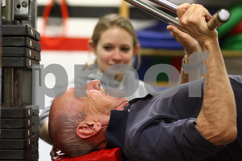 Kyle Bursaw – kbursaw@shawmedia.com<br /> <br /> Stan Trail, 81, uses a machine to lift  weights as Rebekka Juszczak, a Northern Illinois student majoring in rehab services, looks on in the fitness center at Oak Crest on Friday, Nov. 18, 2011.