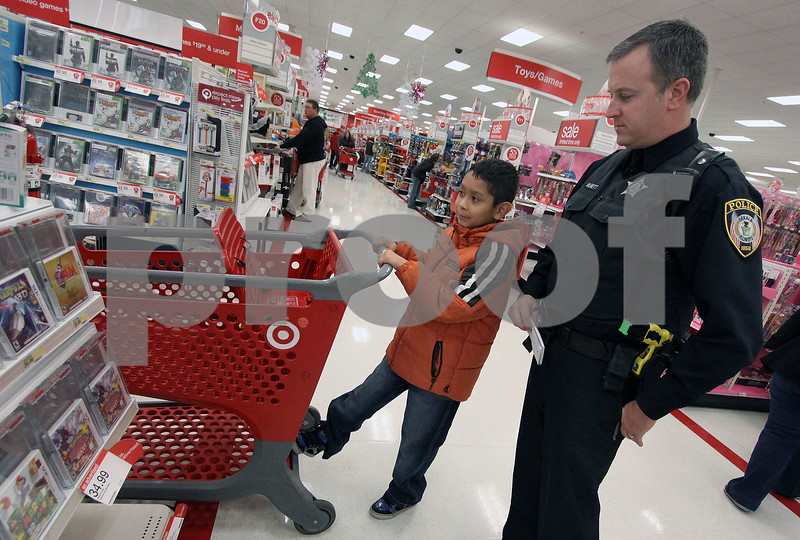 Wendy Kemp - For The Daily Chronicle<br /> DeKalb police officer Chad McNett helps Jonathon Martinez, 9, pick out a video game during the Shop with a Cop event at Target on Sunday.<br /> DeKalb 12/11/11