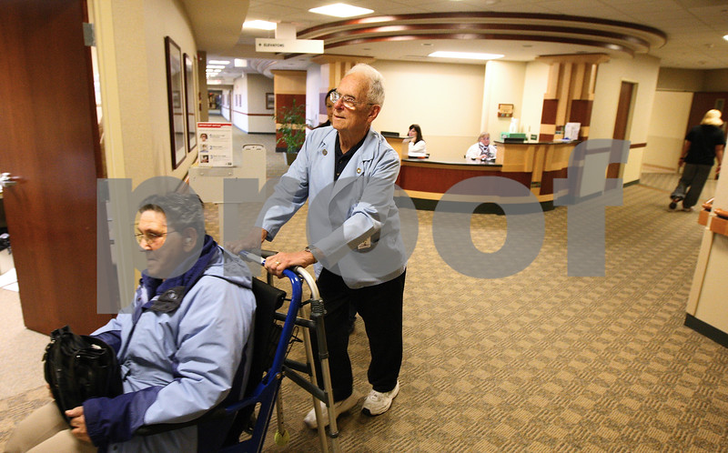 Kyle Bursaw – kbursaw@shawmedia.com<br /> <br /> Norm Schaeffer, a volunteer at Kishwaukee Community Hospital, pushes Clara Petigo to the room of a patient she came to visit on Thursday, Dec. 15, 2011.