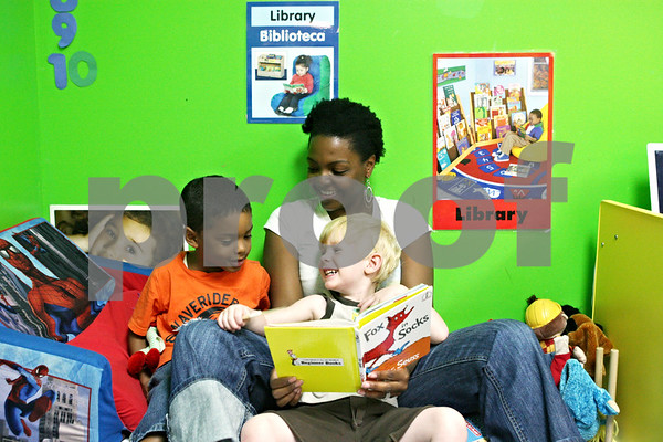 Rob Winner – rwinner@daily-chronicle.com<br /> <br /> At Once Upon a Child Care in Sycamore on Monday afternoon, lead pre-school teacher April Aaron reads to Xavier Dandridge (left), 5, and Chase Trautvetter, 3.
