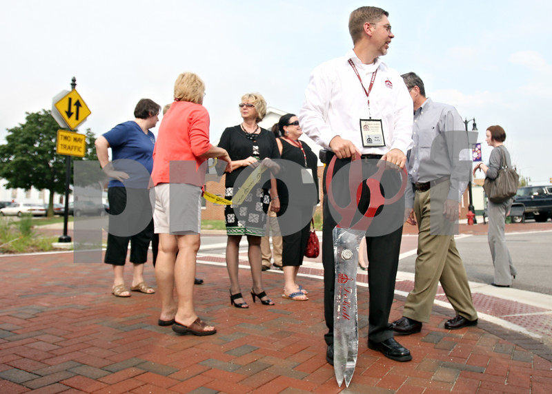 Rob Winner – rwinner@daily-chronicle.com<br /> <br /> At the corner of Locust and Third streets in DeKalb on Thursday evening, Matt Duffy, of the DeKalb Chamber of Commerce, holds a pair of giant scissors as Re:New DeKalb hosted a downtown public improvements ribbon cutting.