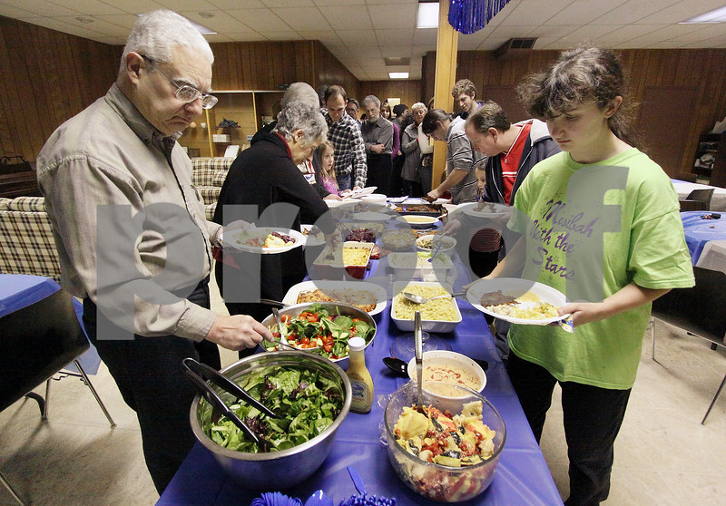 Wendy Kemp - For The Daily Chronicle<br /> Party guests begin dinner at Congregation Beth Shalom on Sunday in DeKalb.<br /> DeKalb 12/18/11