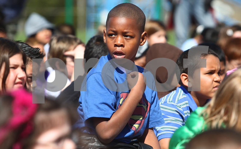 Kyle Bursaw – kbursaw@daily-chronicle.com<br /> <br /> During a school assembly on the playground of Littlejohn Elementary in DeKalb, Ill., My'Kel Childs reacts as he realizes that they are talking about his story of waking up his mom by banging on the window when he came home to find his kitchen on fire. Despite rather appropriately wearing a Superman t-shirt, eight-year-old Childs was unaware that he would be presented with a heroism award on Wednesday, May 4, 2011.