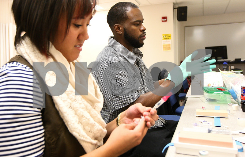 Kyle Bursaw – kbursaw@shawmedia.com<br /> <br /> Quincy Kimble pulls his gloves on as he prepares to give injections to a practice pad (on table) with classmate Kharisa Chapple (left) in their Maternal Health Nursing class at Kishwaukee College on Tuesday, Oct. 25, 2011. Kimble, 25, returned to school in the summer of 2009 after being laid off earlier that year. He is scheduled to complete his nursing degree in May 2012.