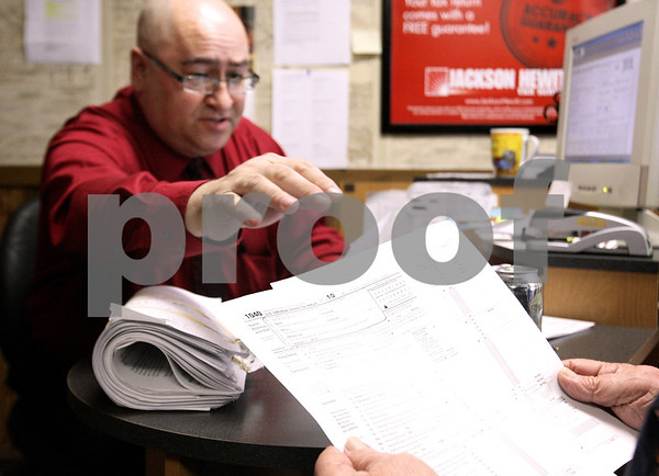 Kyle Bursaw – kbursaw@daily-chronicle.com<br /> <br /> John Saponari hands off a 1040 form to Bjarne 'Bob' Christensen at Jackson Hewitt Tax Service in DeKalb, Ill. on Thursday, Feb. 17, 2011.