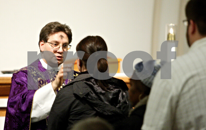 Rob Winner – rwinner@daily-chronicle.com<br /> <br /> Father Matthew Camaioni distributes ash crosses during Ash Wednesday mass at Newman Catholic Student Center in DeKalb.