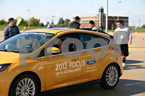 Jeff Engelhardt – NIU students take part in the Ford Focus Laser Hunt Challenge Thursday in the parking lot of the NIU Convocation Center. Drivers had to maneuver around a closed-course with enough precision to trigger laser-activated targets.