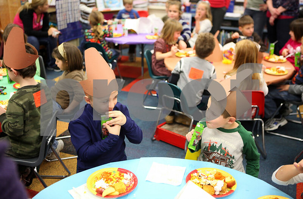 Kyle Bursaw – kbursaw@shawmedia.com<br /> <br /> Collin Kallhoff (left) and Andrew Dries exchange glances as they partake in a Thanksgiving feast while wearing pilgrim hats in a kindergarten classroom at Davenport Elementary School in Genoa, Ill. on Tuesday, Nov. 22, 2011.