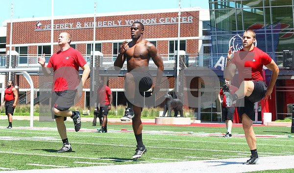 Kyle Bursaw – kbursaw@daily-chronicle.com<br /> <br /> Jordan Delegal (center) and Chandler Harnish (right) perform high knees with other NIU players during a workout session at Huskie Stadium on Tuesday morning.<br /> <br /> <br /> Tuesday, June 28, 2011.