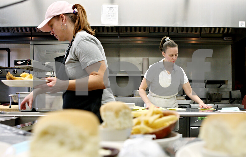Rob Winner – rwinner@daily-chronicle.com<br /> <br /> Becky Curce (left) and Kathy Mohr prepares fried fish dinners at the Knights of Columbus Council 717 on Friday night in DeKalb.