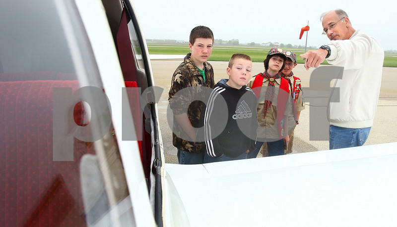 Kyle Bursaw – kbursaw@daily-chronicle.com<br /> <br /> Cooper Hoffman (from left), Tucker Hoffman, Brendan Kaplan, and Henry Plamondon look inside the cockpit as Kevin Frank explains different parts of his plane to children during the EAA Young Eagles Rally at the DeKalb Taylor Municipal Airport on Saturday, June 11, 2011.