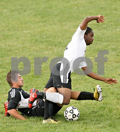 Rob Winner – rwinner@shawmedia.com<br /> <br /> Kaneland's Thanasi Pesmajoglou (left) trips up Sycamore's Michael Coulibaly during the first half in Sycamore, Ill., on Tuesday, Sept. 27, 2011. Kaneland defeated Sycamore, 2-0.