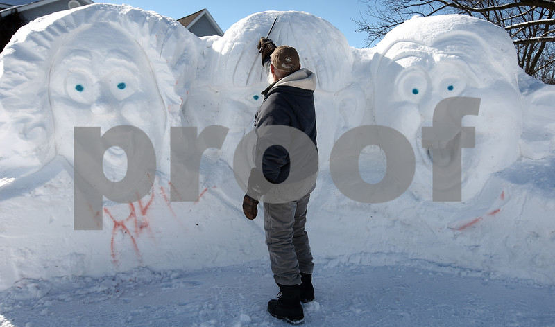 Kyle Bursaw – kbursaw@daily-chronicle.com<br /> <br /> Lynden W. Bute works on Moe in the center of his Three Stooges snow sculpture in his yard, visible from Main street in Sycamore, Ill. on Tuesday, Feb. 8, 2011.