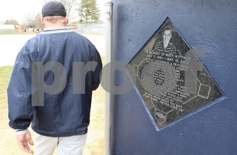 Kyle Bursaw – kbursaw@daily-chronicle.com<br /> <br /> Hiawatha assistant baseball coach Mark Wittwer walks past a plaque on the side of the dugout before a game on Wednesday, April 6, 2011. The batting cage and dugouts at Hiawatha's baseball field are dedicated to Wittwer's son, Matt, who died of leukemia in 2010.