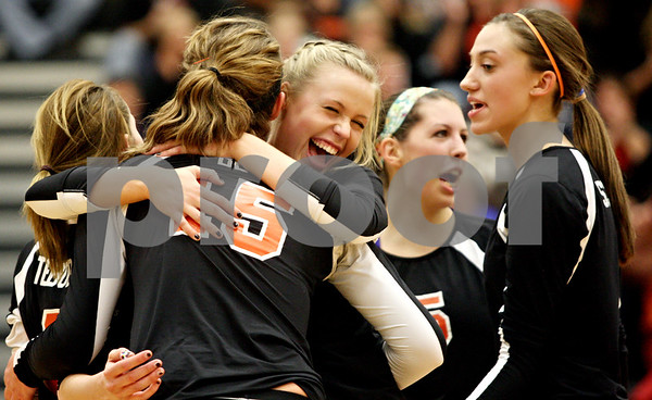 Rob Winner – rwinner@shawmedia.com<br /> <br /> DeKalb's Emily Bemis (15) is hugged by teammate Baleigh Euhus after the last point in the first game in DeKalb on Thursday, Oct. 20, 2011. Dekalb defeated Morris, 25-19, 18-25 and 25-23.