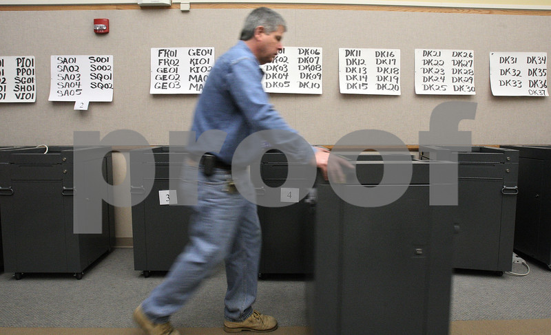 Kyle Bursaw – kbursaw@daily-chronicle.com<br /> <br /> Jim Herrmann, sets up ballot counting and collection devices for early voting in the Legislative Center at 200 N. Main street in Sycamore, Ill. on Friday, March 11, 2011.
