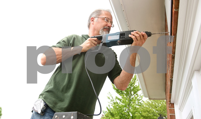 Kyle Bursaw – kbursaw@daily-chronicle.com<br /> <br /> Carpenter Phil Bennett drills a hole through the sign to the Glidden Welcome Center during the process of putting up the sign on Thursday, May 19, 2011.