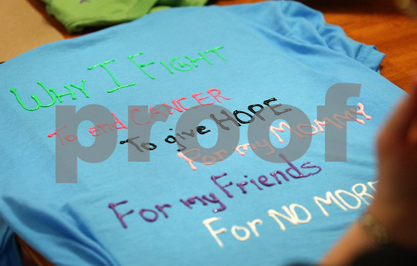 Kyle Bursaw – kbursaw@daily-chronicle.com<br /> <br /> Julianna Ladas wrote some of the reasons she participates in Relay for Life on the back of a shirt she will wear during the upcoming Relay for Life. The entire family made shirts at their Sycamore home on Saturday, May 21, 2011.