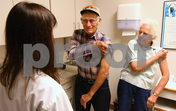 Kyle Bursaw – kbursaw@shawmedia.com<br /> <br /> Orrin and Marion Vandeburg (center and right) roll up their sleeves for public health nurse Patti Burke (left) to administer an influenza vaccination at the DeKalb County Health Department on Thursday, Sept. 22, 2011.