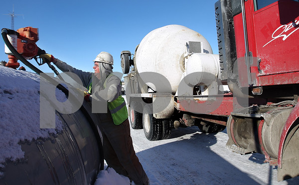 Kyle Bursaw – kbursaw@daily-chronicle.com<br /> <br /> Gary Greer, a driver for Ozinga Ready Made Concrete, returns the diesel pump to the tank after refueling the truck he drove on the morning of Thursday, Feb. 10, 2011 in Sycamore, Ill.