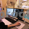 Kyle Bursaw – kbursaw@daily-chronicle.com<br /> <br /> In a demonstration for the Daily Chronicle, Joni Simone, the lead C.T. technologist at Kishwaukee Hospital, uses new CT scanning software that creates images of similar diagnostic quality with less radiation use on patients, as fellow hospital employee Noah Nordbrock lays in the scanning bed on Wednesday, Jan. 26, 2011.