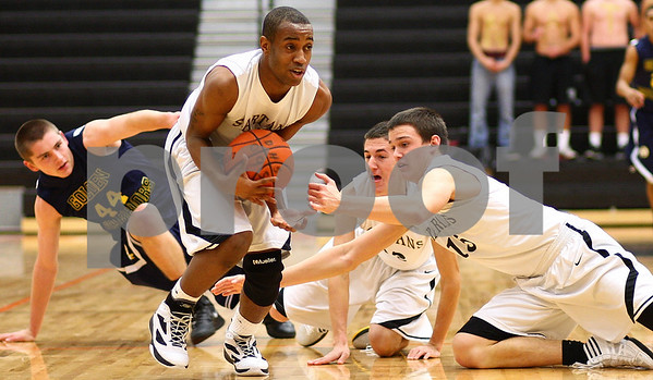 Kyle Bursaw – kbursaw@shawmedia.com<br /> <br /> Sycamore guard Rashaud Bomar (standing) scoops up a loose ball, also chased by Sterling's Patrick Petrosky (left), Sycamore's Kyle Buzzard (back) and Devin Mottet (right), that was nearly stolen by Sterling in the first quarter of their match in the Chuck Dayton Holiday Tournament at DeKalb High School on Friday, Dec. 23, 2011. Sterling defeated Sycamore 61-41.