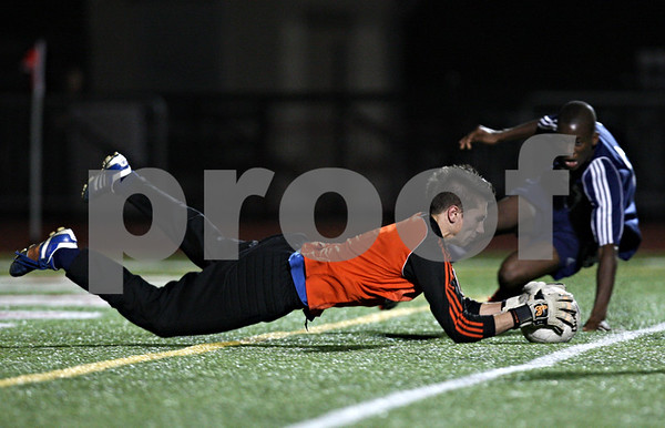 Rob Winner – rwinner@shawmedia.com<br /> <br /> Hinckley-Big Rock goalkeeper Forrest Grivetti make a diving save in front of Lisle's Alhaji Kamara during the first overtime of a Class 1A Naperville Central Super Sectional on Tuesday, October 25, 2011.