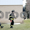 Rob Winner – rwinner@daily-chronicle.com<br /> <br /> Two firefighters walk around the Custom Aluminum Product building in Genoa after it had been evacuated because of a hazardous material leak.