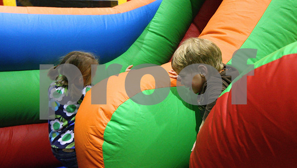 Kyle Bursaw – kbursaw@shawmedia.com<br /> <br /> Siblings Lily (left) and Mason Depauw make their way through obstacles to the slide at the top of the inflatable structure at 'Jumping Jolidays' hosted by Jumpy Jumpers at Cornerstone Christian Academy on Wednesday, Dec. 21, 2011.