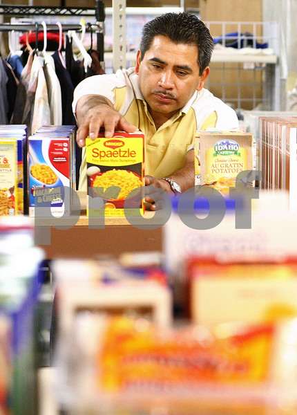 Kyle Bursaw – kbursaw@daily-chronicle.com<br /> <br /> Gregario Reyes stocks the shelves at the Salvation Army Food Pantry in DeKalb, Ill. on Thursday, June 16, 2011.
