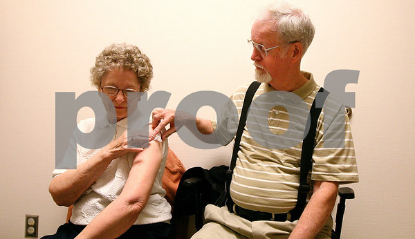 Kyle Bursaw – kbursaw@shawmedia.com<br /> <br /> Gil Larimer helps Alice Larimer hold gauze on the spot where Alice received an influenza vaccination as she waits for a bandage at the DeKalb County Health Department on Thursday, Sept. 22, 2011.
