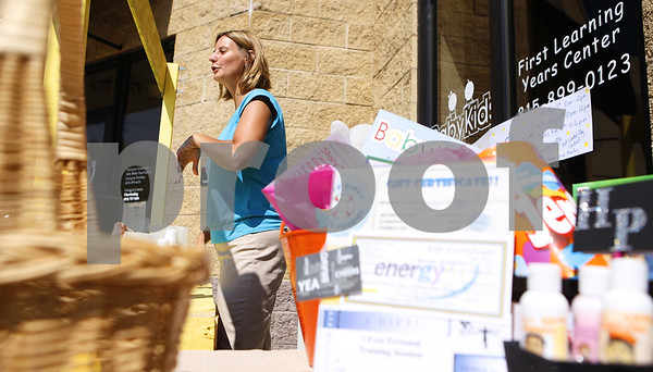 Kyle Bursaw – kbursaw@daily-chronicle.com<br /> <br /> Cheryl Connelly, director of BabyKids First Learning years in Sycamore, Ill. explains Alex's Lemonade Stand to a passerby, The stand sells lemonade and raffle tickets in exchange for donations. Tuesday, Aug. 9, 2011.