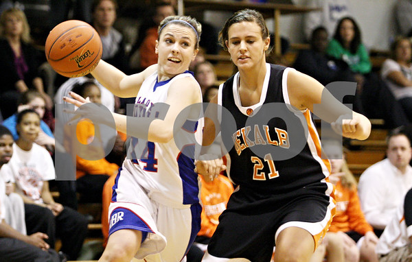 Rob Winner – rwinner@daily-chronicle.com<br /> <br /> Hinckley-Big Rock's Kaitlin Phillips (left) moves past DeKalb defender Kelli Gerace on her way to the basket during the first quarter.