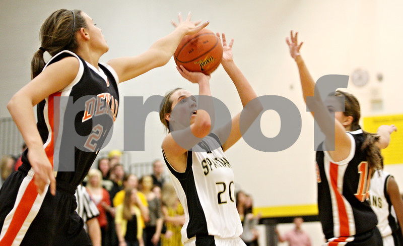 Rob Winner – rwinner@daily-chronicle.com<br /> <br /> DeKalb's Kell Gerace (left) tries to block a shot by Sycamore's Ashley Berlinski during the first quarter on Thursday, Feb. 10, 2011 in Sycamore, Ill. Sycamore went on to defeat DeKalb, 34-30.